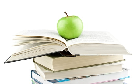 Green apple on the expanded textbook on white background Stock Photo