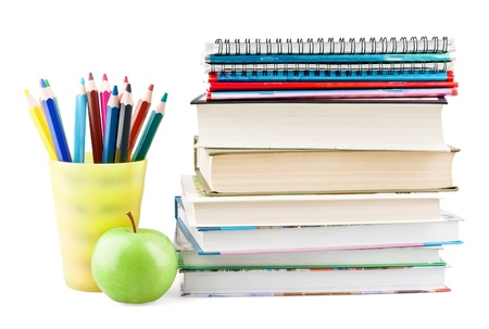 Coloured pencils in jar with textbooks and apple on white background Stock Photo