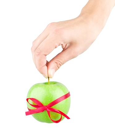 Gift ribbon tied with green apple and hand on white background photo