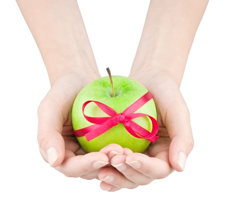 Apple with ribbon in womens hands on white backlground