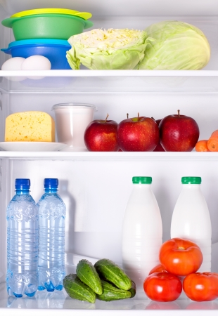 Refrigerator full of healthy food. Vegetables, fruits, water and dairy products  photo