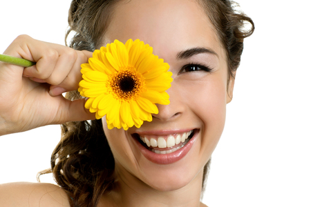 Portrait of young smiling beautiful woman with a gerbera on white background  photo