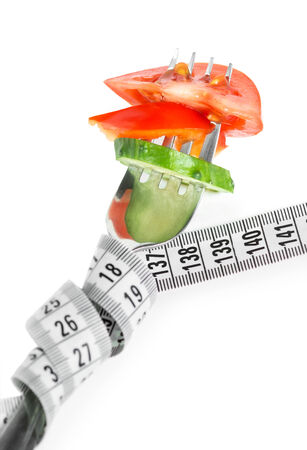 diet concept: Fresh vegetables on fork with measuring tape. Diet concept