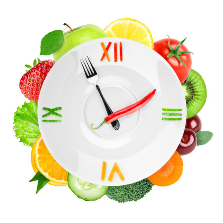 Healthy food concept. Fruits and vegetables. Food clock on white background photo