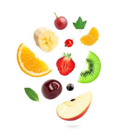 Falling fresh fruits and berries on white background photo