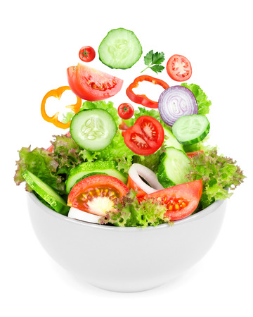 Fresh salad. Mixed falling vegetables in bowl on white background photo