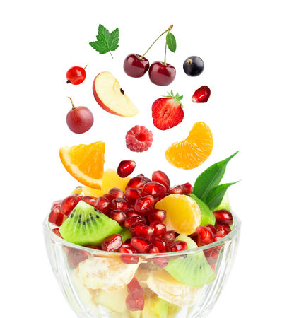 mixed fruits: Fresh healthy fruit salad. Mixed falling berries and fruits in bowl on white background