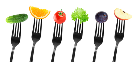 diet concept: Fruits and vegetables on fork. Diet concept