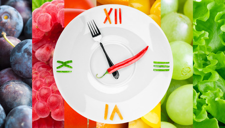 eating dinner: Food clock with vegetables and fruits as background. Healthy food concept
