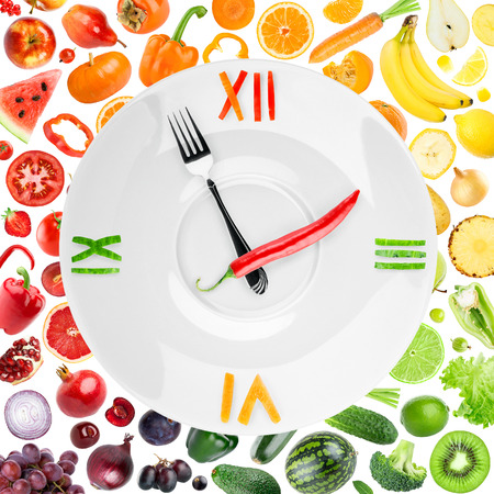 Food clock with vegetables and fruits. Healthy food concept 免版税图像