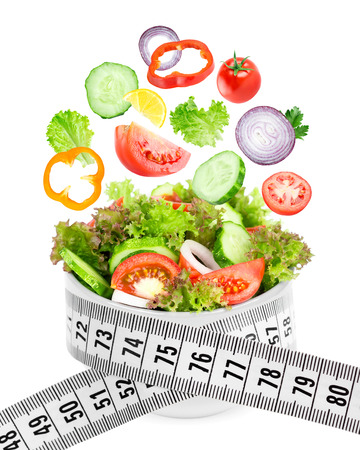 diet concept: Fresh salad. Mixed falling vegetables in bowl on white background. Diet concept