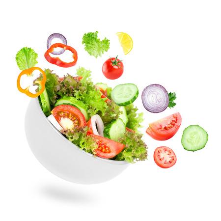 ensalada verde: Ensalada fresca. Hortalizas a que mezclados en un taz�n en el fondo blanco Foto de archivo