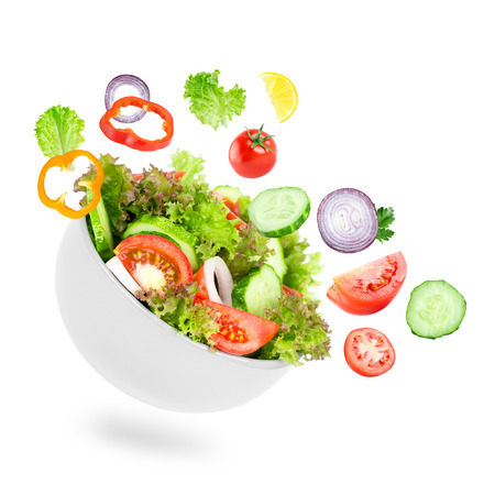 mixed vegetables: Fresh salad. Mixed falling vegetables in bowl on white background