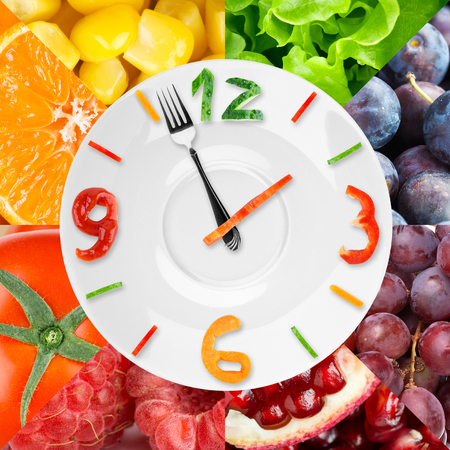 Tiempo: Reloj de Alimentos con verduras y frutas como fondo. Concepto de alimentos saludables