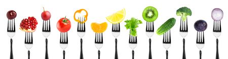 Color fruits and vegetables on fork on white background. Fresh food Standard-Bild