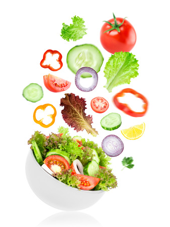 salad bowl: Fresh salad. Mixed falling vegetables in bowl on white background