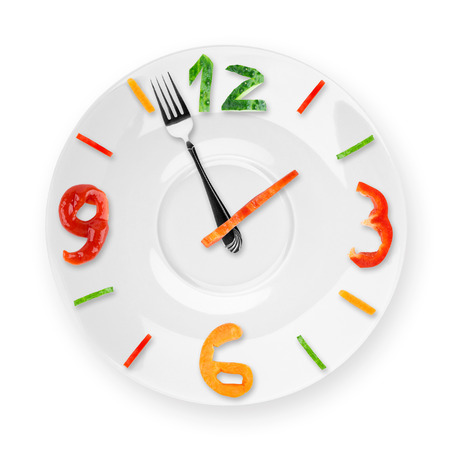 Food clock on white background. Healthy food concept
