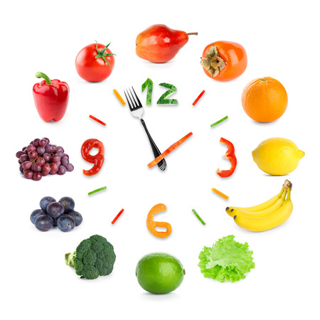 food concept: Food clock with fruits and vegetables on white background. Food concept
