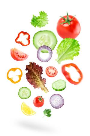 La caída de las verduras frescas en el fondo blanco