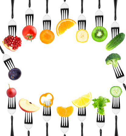 Fruits and vegetables on fork on white background. Fresh food