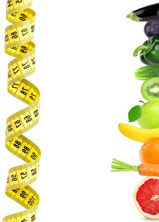 cintas: frutas y hortalizas frescas con cinta métrica sobre fondo blanco. Concepto de la dieta. Comida sana Foto de archivo