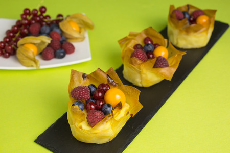 mini cheesecakes with filo pastry and different berries on top