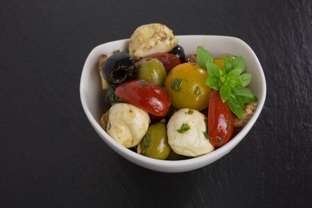 antipasti: Mediterranean antipasti salad with mozzarella balls, green and black olives and cherry tomatoes and some tiny-leafed basil.