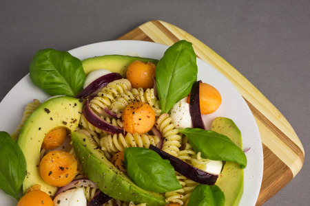 pasta salad: pasta salad consisting of fusili with mozzarella and melon with avocado and red onions Stock Photo