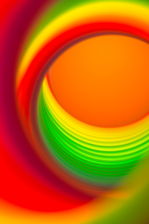 slinky: view through a vibrant rainbow colored spring with selective focus