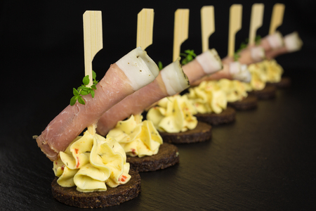 pumpernickel: appetizer of rolled ham with cream cheese on mustard dip and pumpernickel