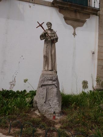 statue of saint holding cross in church back garden