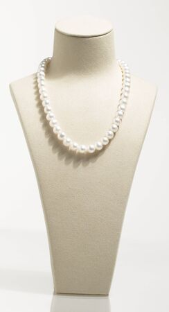 Pearl necklace on white mannequin isolated photo
