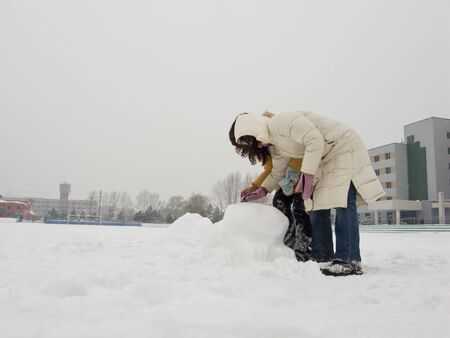 Girls are  playing the snow