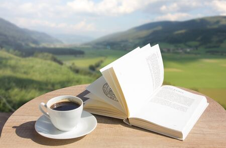 Coffee cup with open book over Austrian Alps