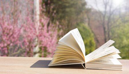Open book on wooden table over spring garden