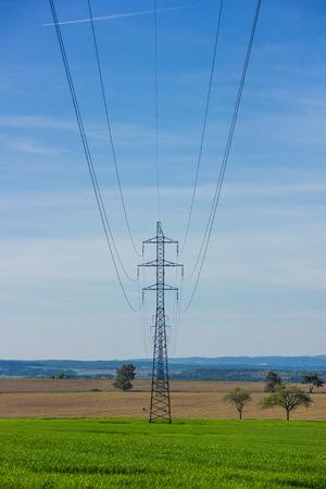 Powerline in groen veld Stockfoto