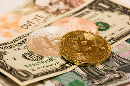 Symbolic coins of bitcoin on banknotes of US dollars, czech crowns and Russian rubles. Stock Photo