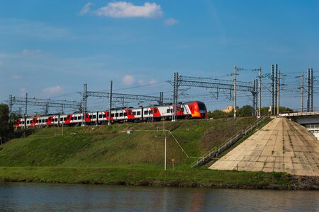 Russian modern high-speed electric train on a bridge. Sunny day.