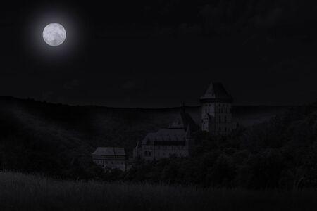 Spooky night over Karlstejn Castle. Full moon. Czech Republic.