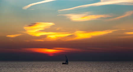 Boat sailing along against a vivid colorful sunset. Gulf of Finland.