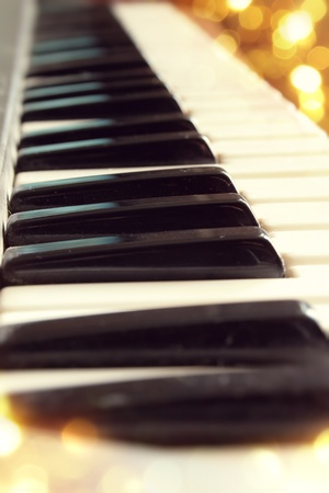 Piano keys close up on a background of bright lights photo