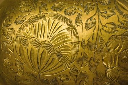 bronze background: Stamping floral pattern on a metal vase