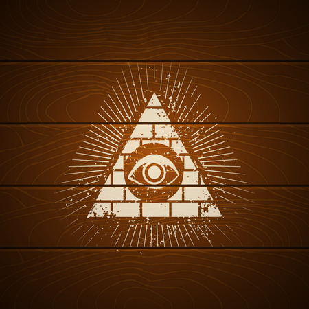 Pyramid with eye on wooden background