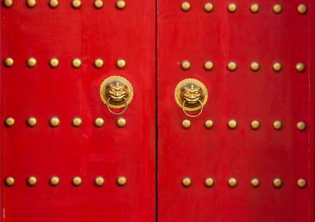 Red door with lion heads in asian style. Red wooden gates with golden details. Stock Photo