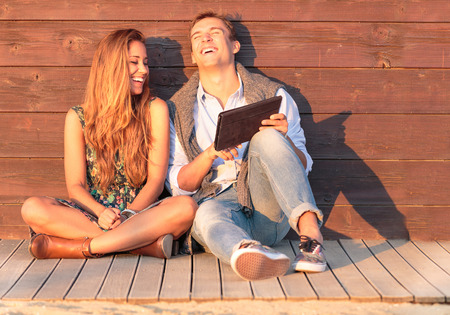 beautiful sunshine: Cheerful guy with girl laugh about video on the tablet. Best friends having fun at the beach with social media and funny contents. Friendship of young people during holiday life moment at sunset.