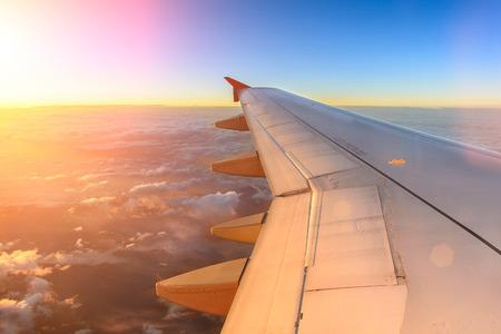 旅行: 夕日の中に飛行機飛ぶから日陰の雲と空の上を飛んで飛行機の空撮。世界中の国際旅行の間に感情的な瞬間の飛行機の窓からの眺め。