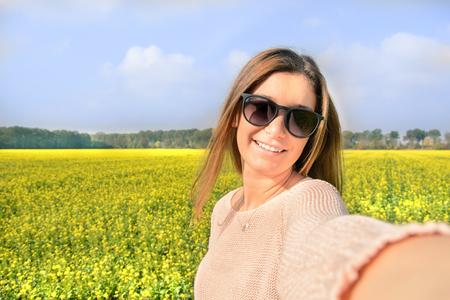 Schöne Frau, die selfie Bild von sich selbst auf dem gelben Gebiet mit der Natur Hintergrund. Close up Portrait einer jungen attraktiven Mädchen in die Kamera während der sonnigen Winternachmittag mit warmem Licht lächelnd.