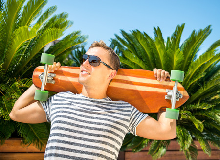 Handsome man leaning against green palms and holding his long board 免版税图像