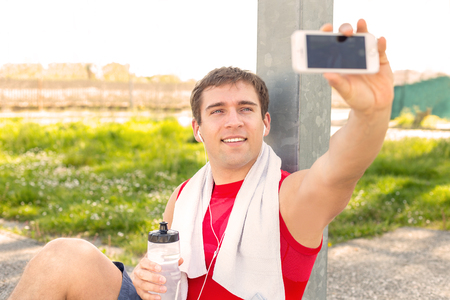 Sitting guy in park and take a selfie during a break at run training with friends - listen music with headphones - Young man finish to do sport and make himself picture - fitness jogging workout