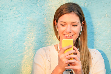 Happy girl connected to social media network and having fun with smartphone. Young woman smiling and typing on the phone against blue wooden background. Lifestyle concept of new trends and technology. 免版税图像